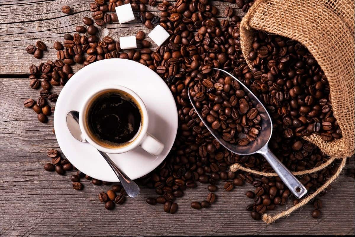 a cup of black coffee next to a bag of roasted beans.