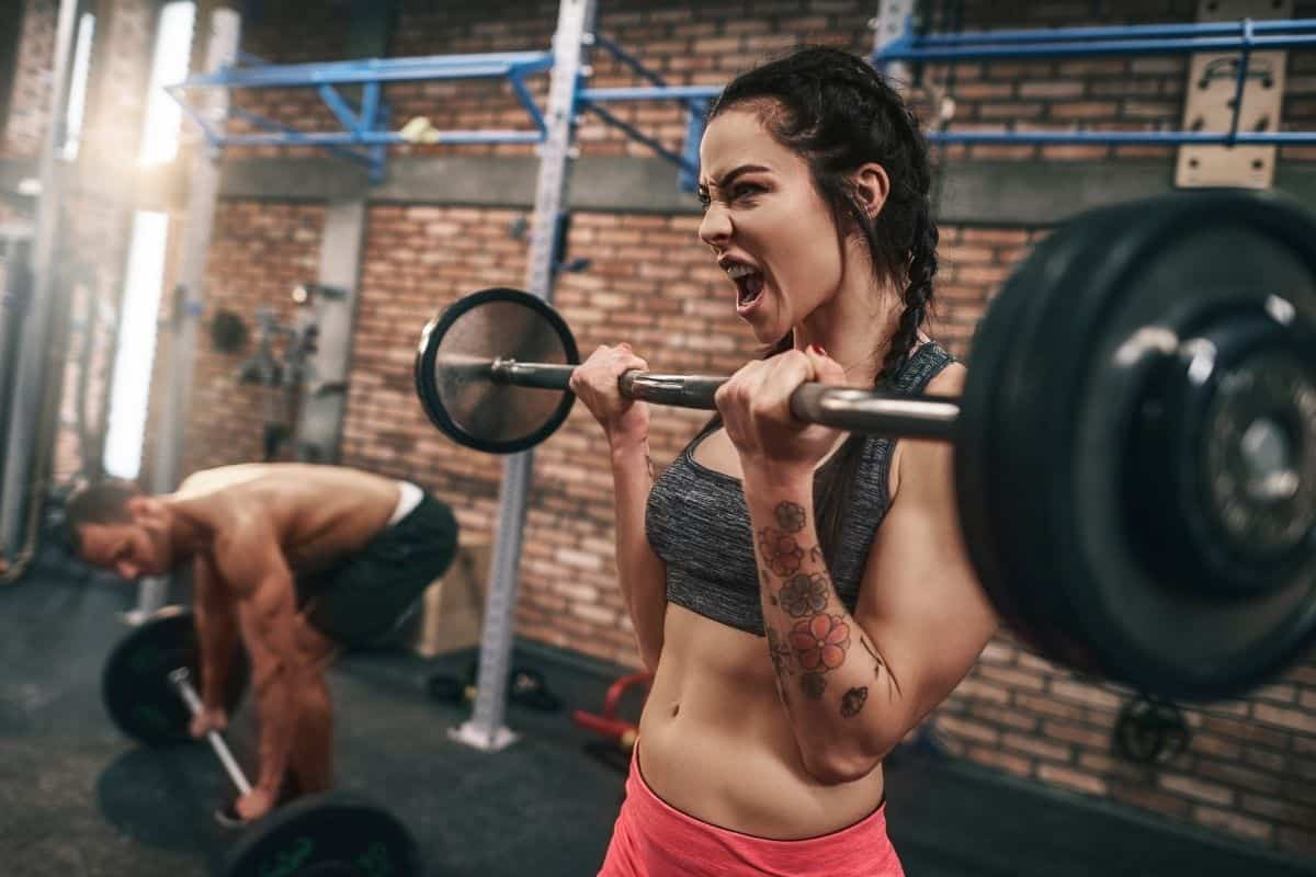 man and woman exercising at gym after having pre-workout coffee.