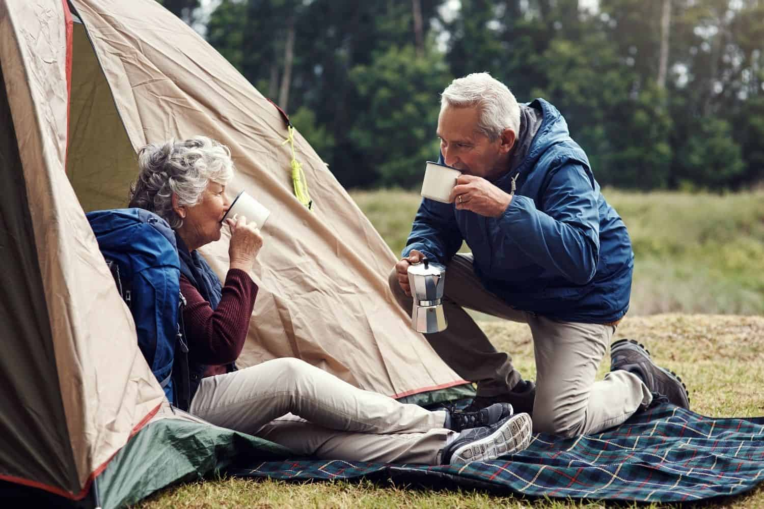 old couple drinking coffee outside their camping tent.
