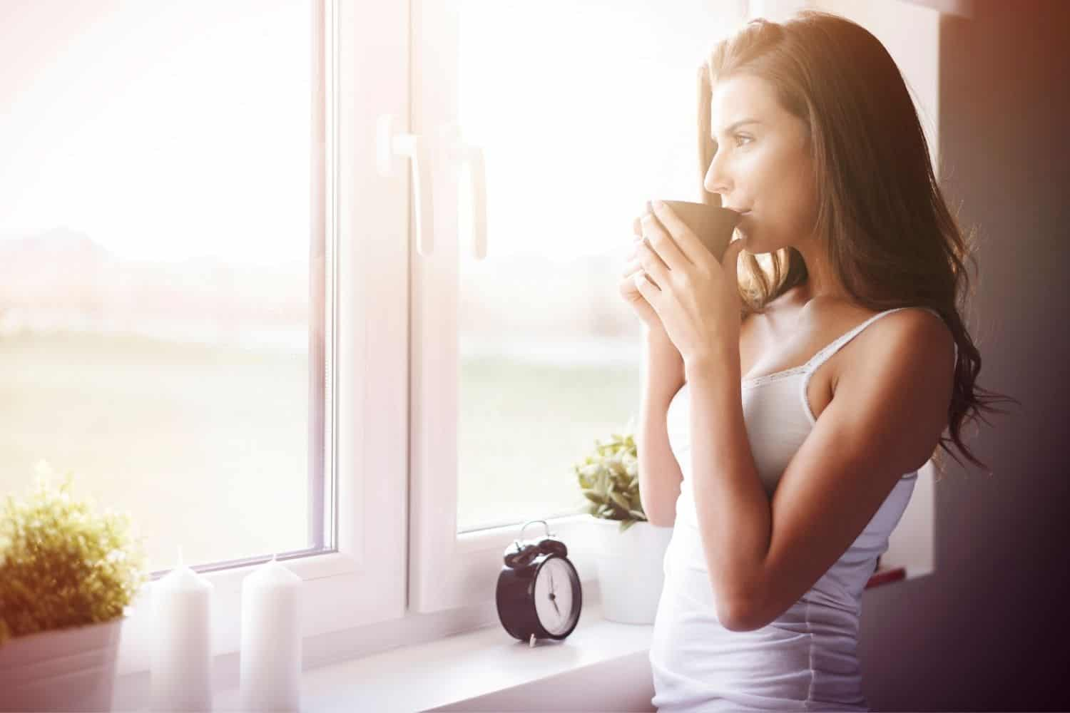 woman drinking her morning coffee to wake her up.