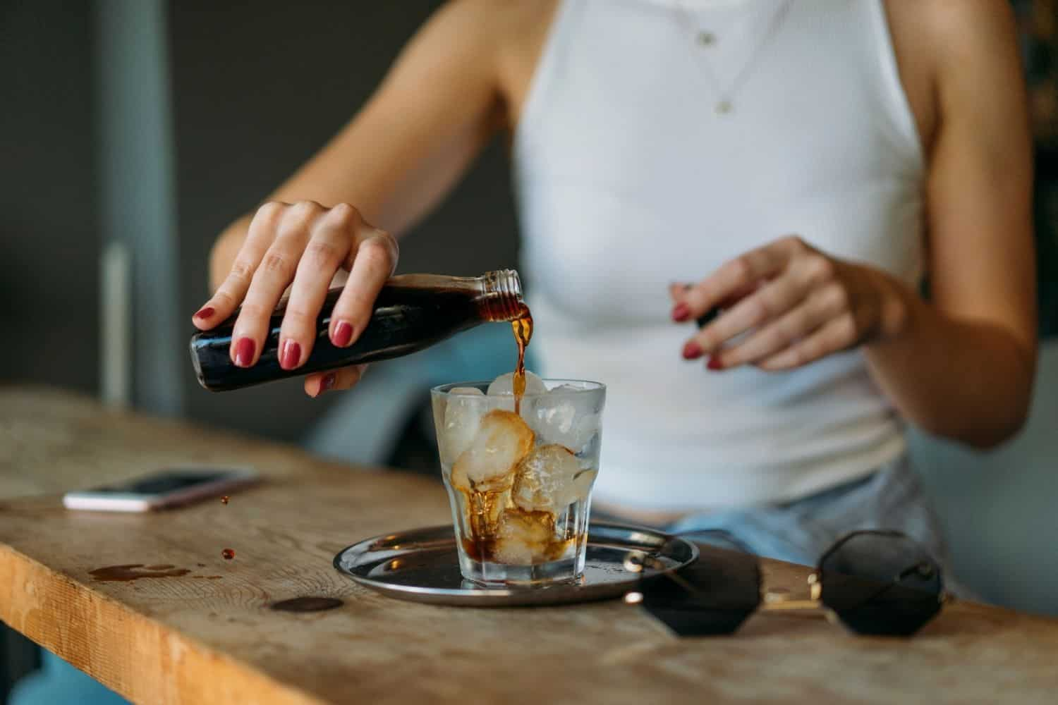 woman pouring cold brew coffee into a glass.