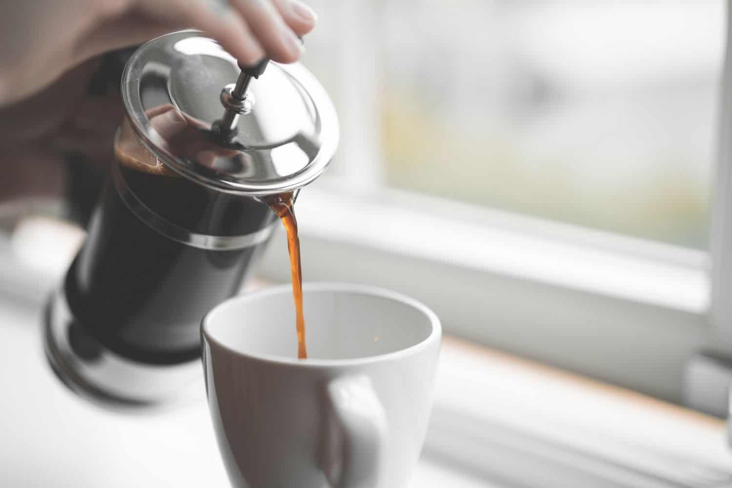 woman pouring french press coffee into a cup.