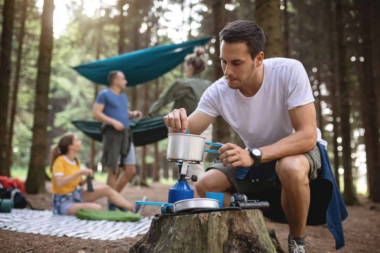 man brewing cowboy coffee while camping.